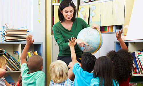 Teacher holding globe in front of young students