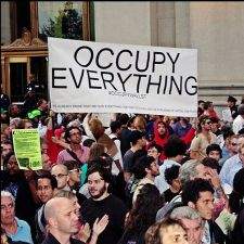 Protestors holding 'Occupy Everything' sign