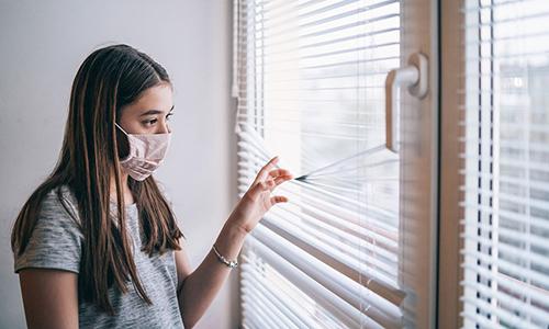 Teen wearing mask looking out window