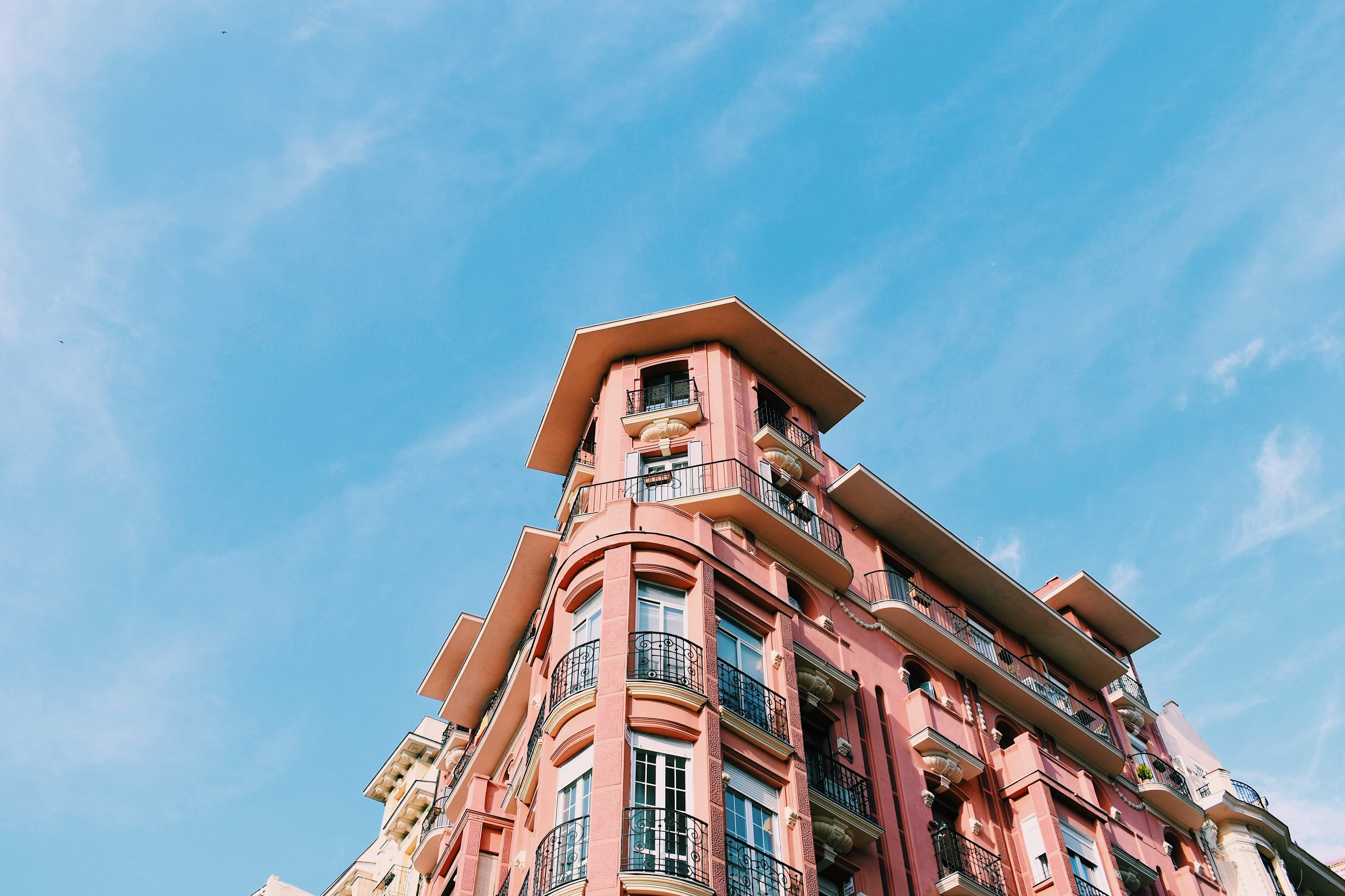 Dramatic pink building set against blue sky with clouds in Madrid