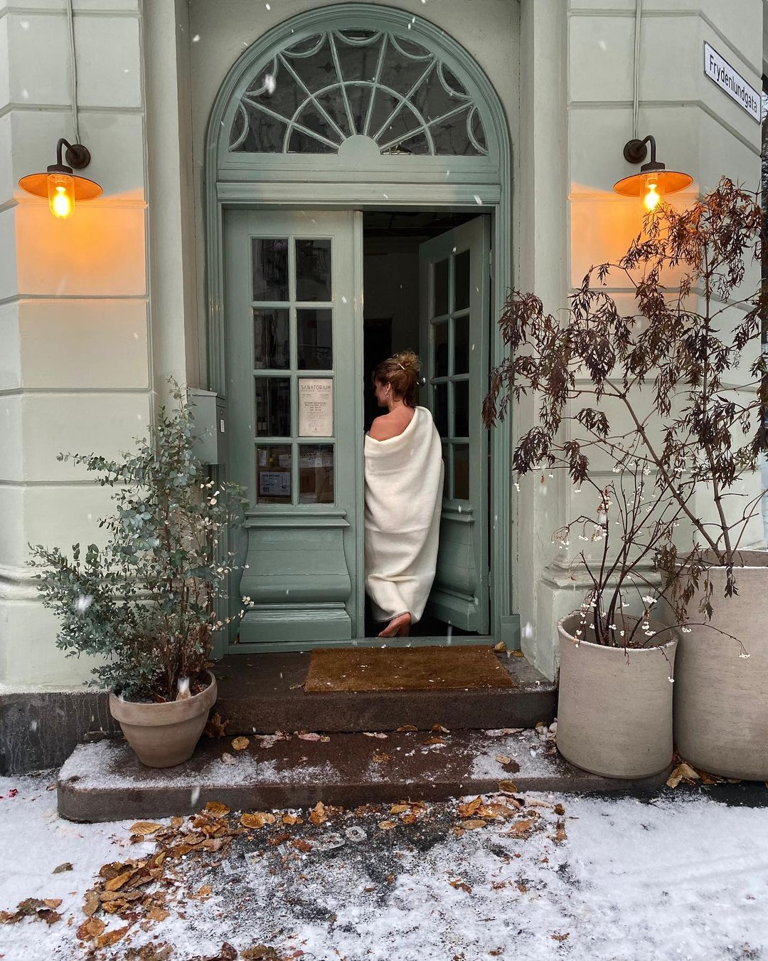 Woman draped in white linen entering a building