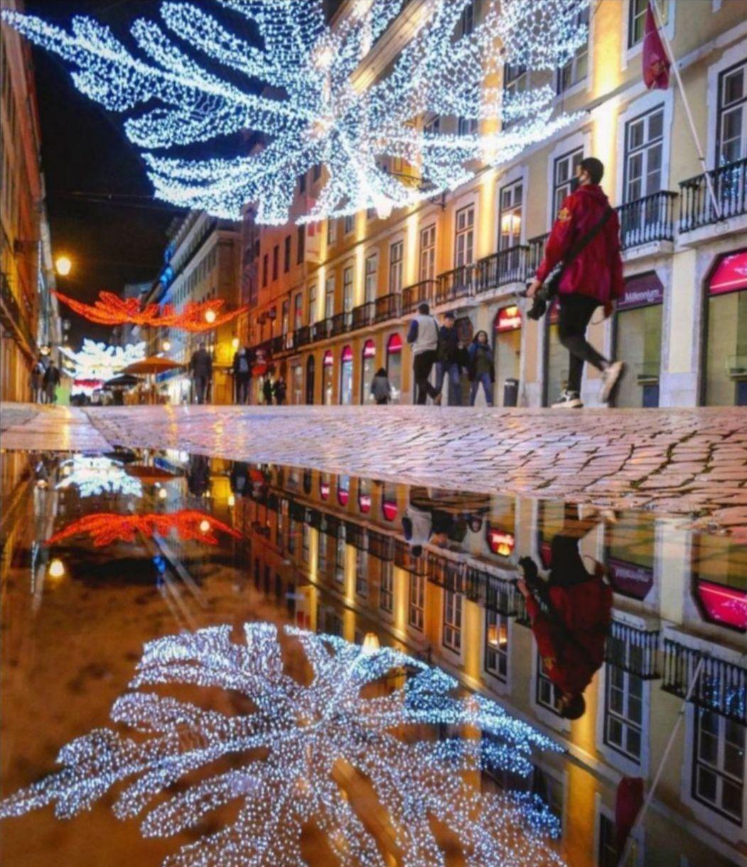 Very festive street shown in water reflection in Lisbon