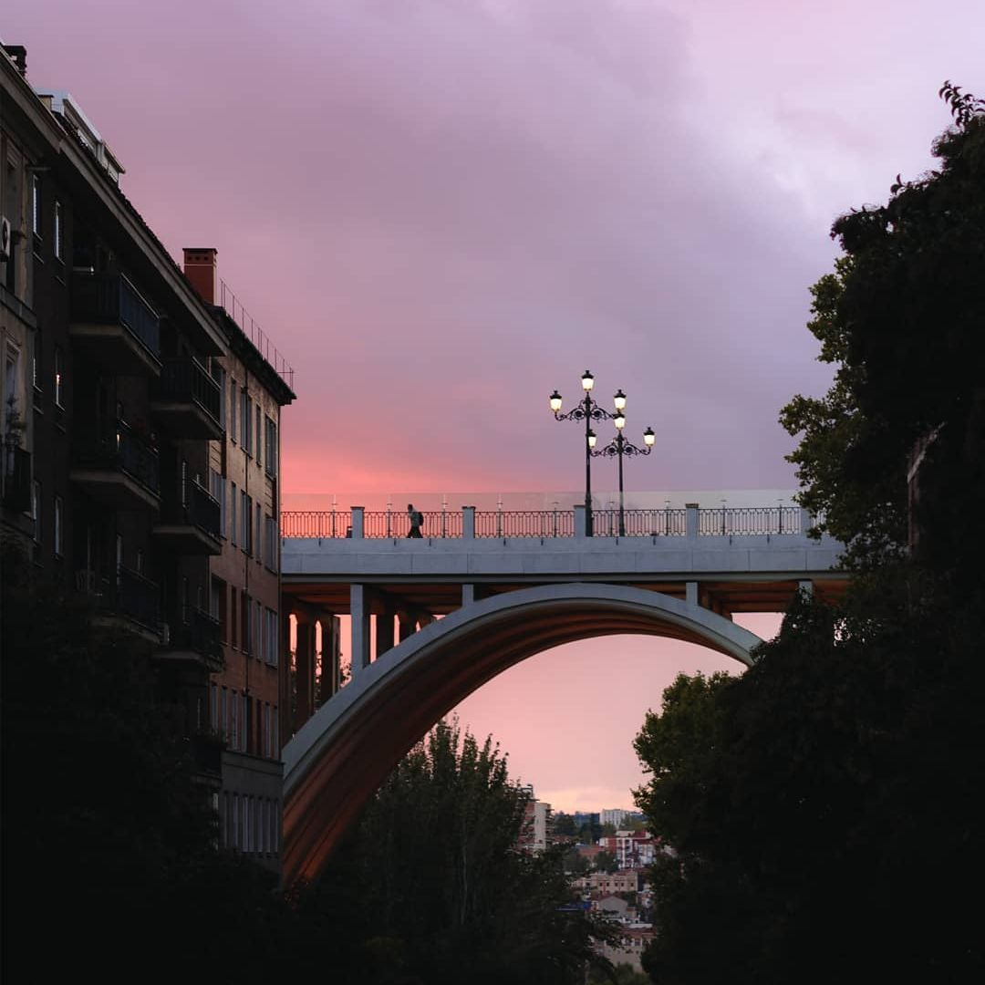 Bridge set in distance with pink and purple sunset in Madrid
