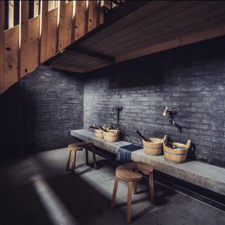 Cozy bench in front of dark walls of sauna