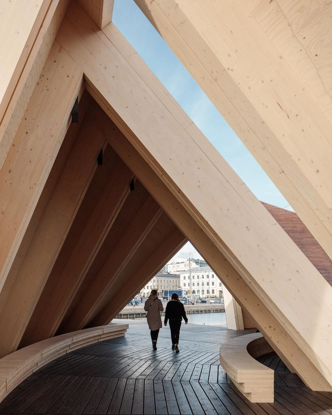 Two figures walking through the dynamic linear wood structure of the Helsinki Biennial Pavilion