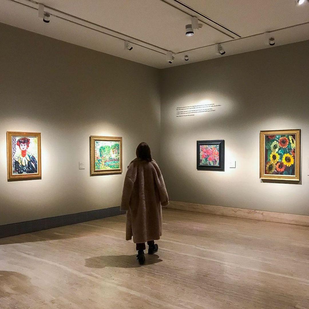Woman in fur coat admiring paintings in a gallery in Madrid