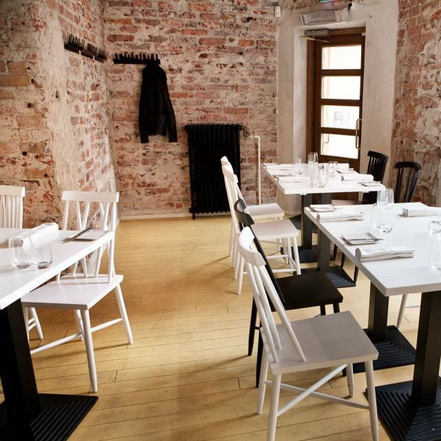Rustic brick walls of dining space with simple clean white tables and chairs in Helsinki