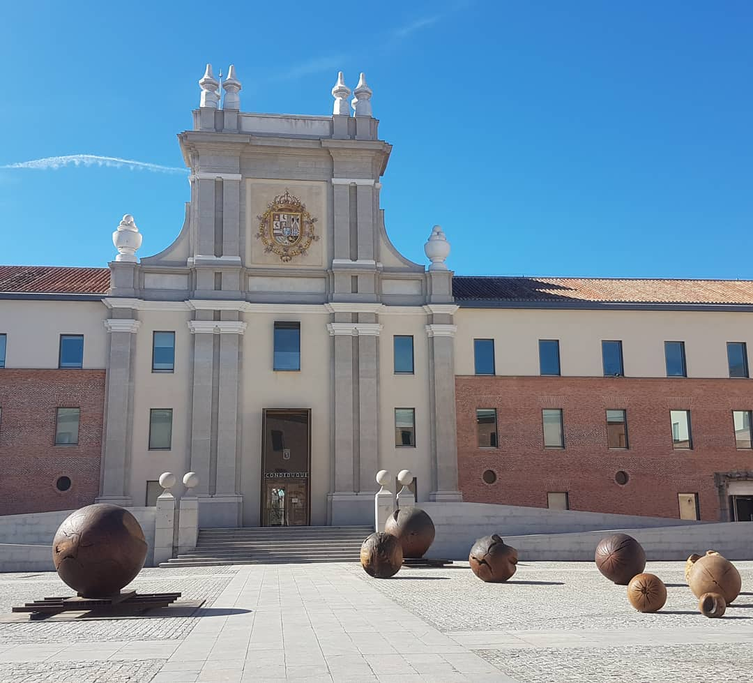 Facade of Conde Duque with blue sky and large metallic balls in front