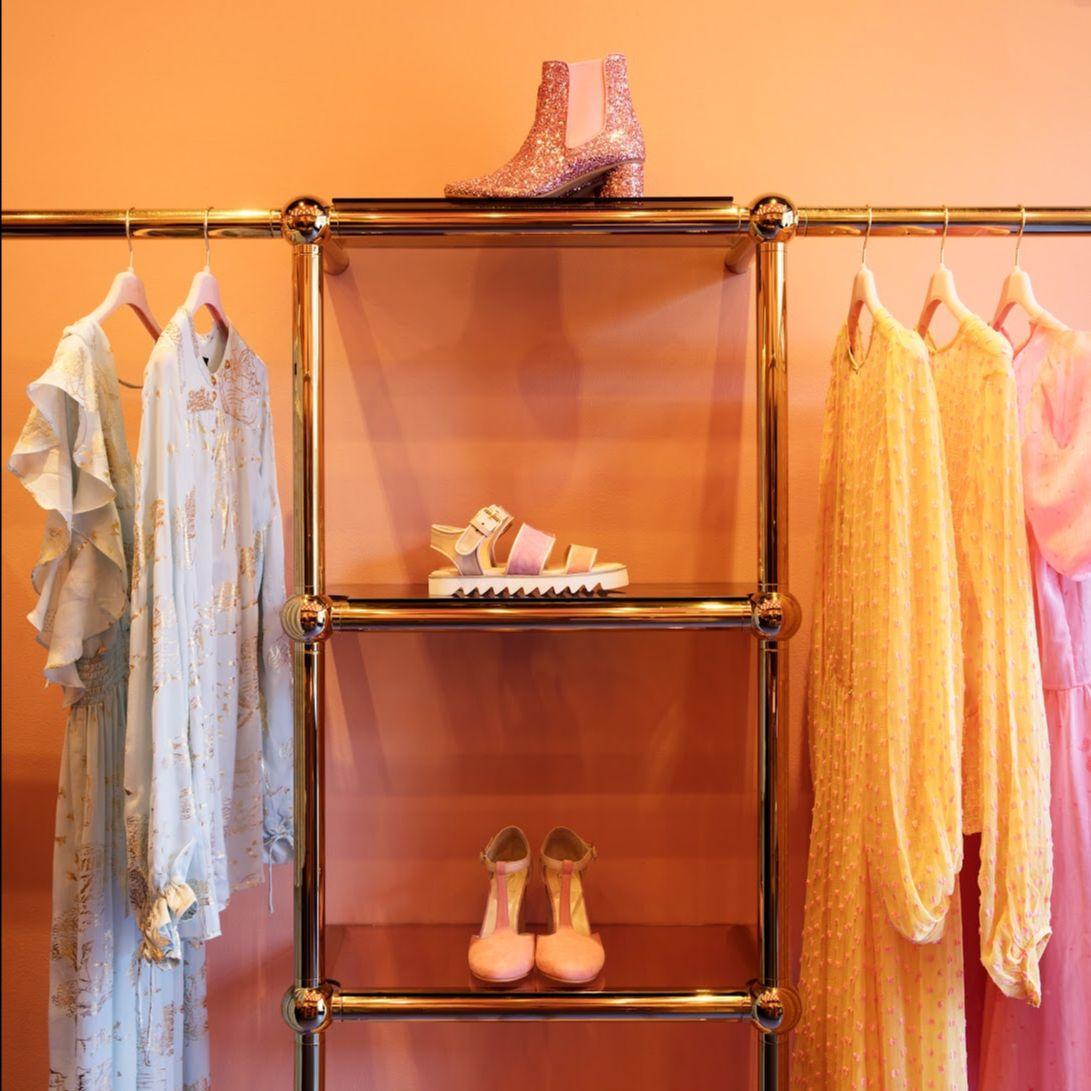 Racks of pastel dresses displayed in Stine Goya's store