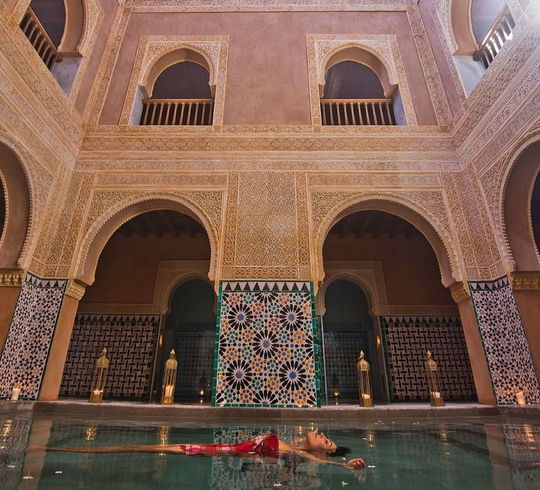 Women in red swimsuit floating in pool with moorish tile on walls