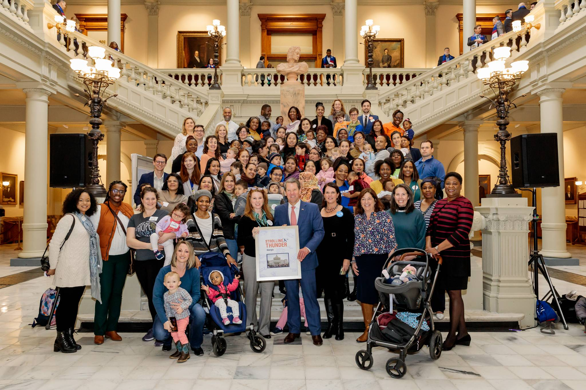 The photo shows a group of around 100 parents with infants and toddlers standing on stairs around Georgia Governor, Brian Kemp.