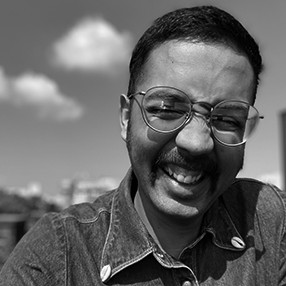 danilo machado— a mustached brown person with round blue glasses and a denim shirt smiles in the sun. Behind them are trees, the city, two white clouds, and blue sky.