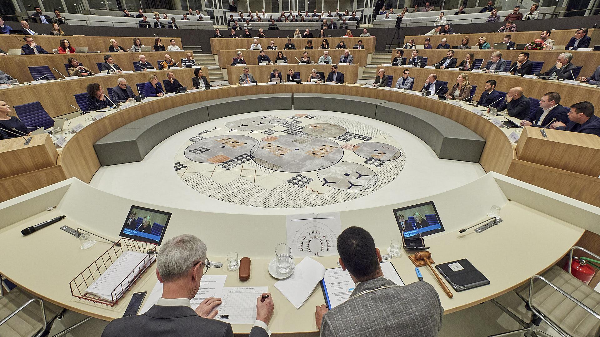 Foto van de raadzaal met raadsleden op hun plek en de burgemeester en griffier op de voorgrond