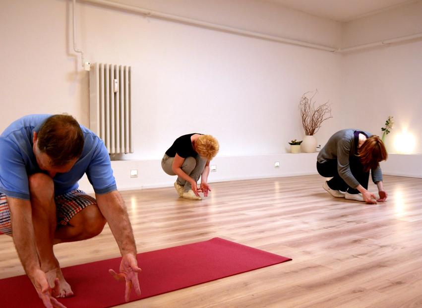3 Personen beim Qigong in Studio mit weißen Wänden und beigem Boden