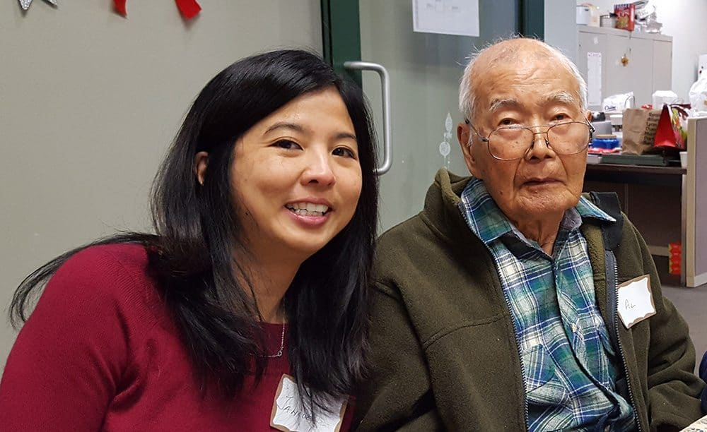 Woman caregiver in red sweater smiling next to older gentleman in a plaid shirt.