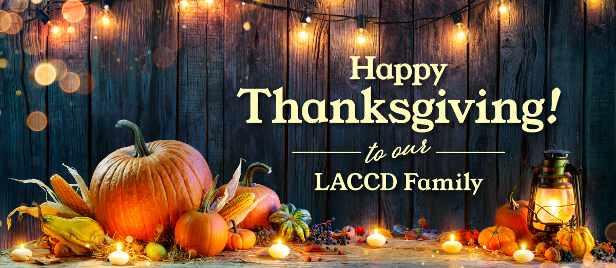 "Image of a rustic wooden table with a fall harvest of pumpkins, squash, and corn atop. Candles are lit and lights are strung in the background. Text reads ""Happy Thanksgiving! To Our LACCD Family"