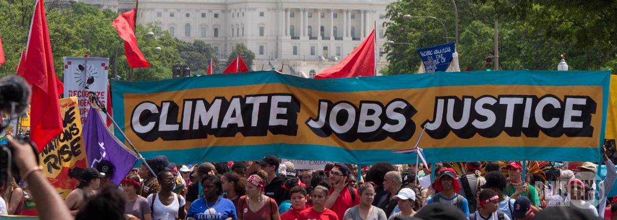"""Photos taken at the 2017 DC Climate March on April 29, 2017. Protestors hold up a banner demanding: """"Climate, Jobs, Justice""""."""