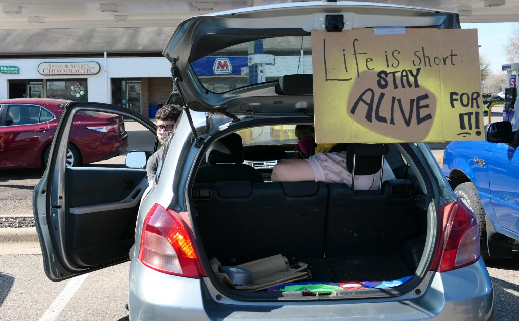 "Protesters in a car outside of Caribou Coffee holding a sign that says ""Life is short, stay alive for it!"""