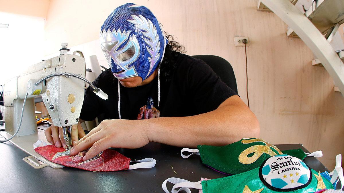 A man wearing a luche libra mask sewing face masks