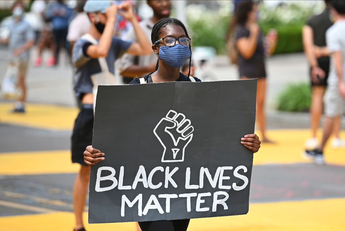 Photo of a young black woman in glasses and mouth covering holding a Black Lives Matter sign during an outdoor protest
