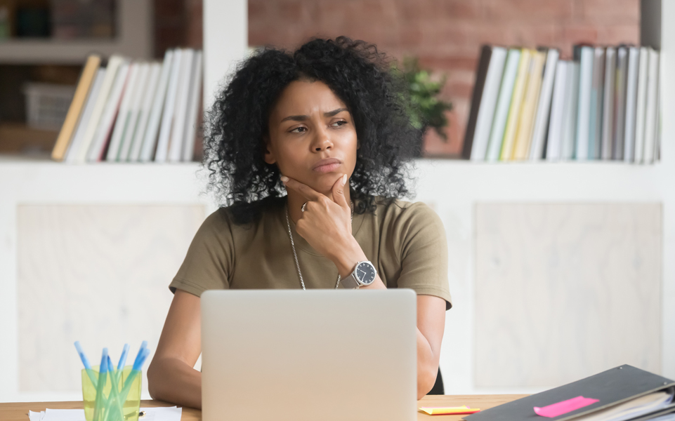 Stock photo of a student of color looking as though she is trying to make a decision.