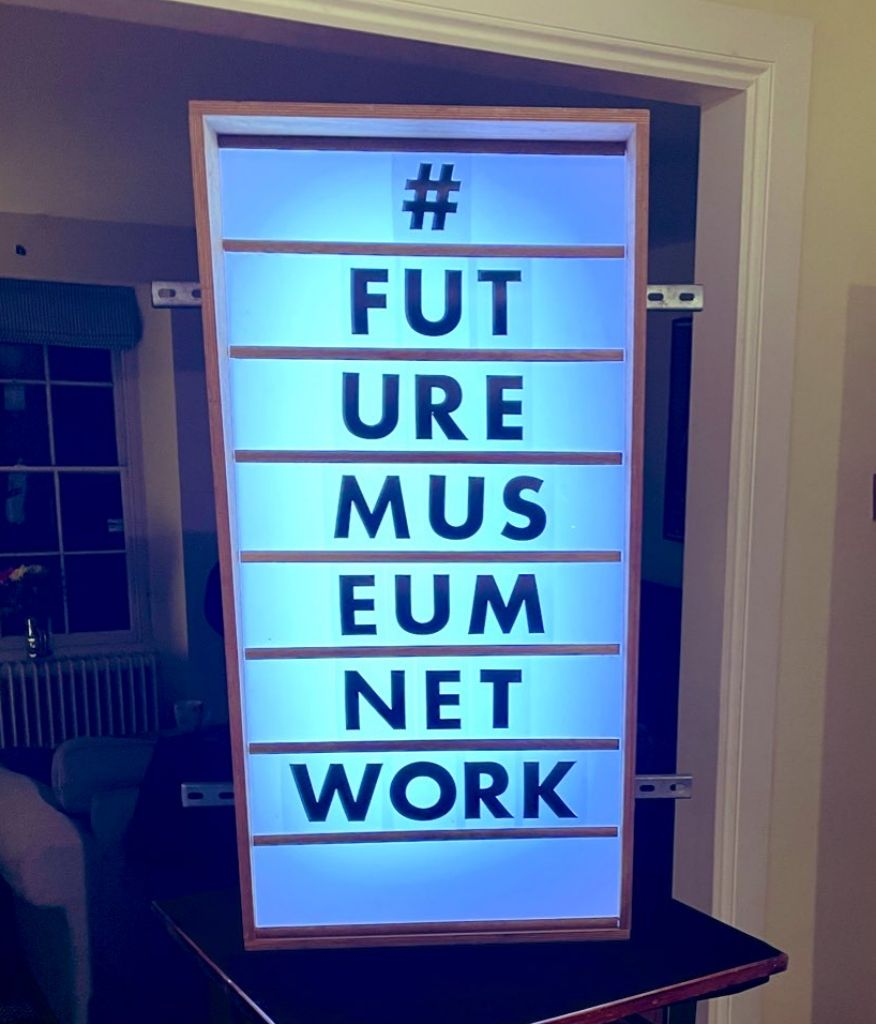 A light display with letters reading down in 6 rows reads '#FUTUREMUSEUMNETWORK'. Artwork by Stuart Robinson.