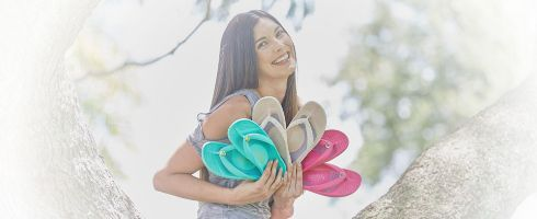 woman sitting in tree holding Cheeks sandals
