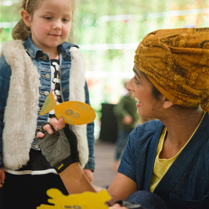 a person wearing a yellow headscarf and fingerless cloves holds a yellow cardboard fish up to a child in a fluffy white vest