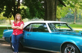 Kathy Gale in front of her blue car