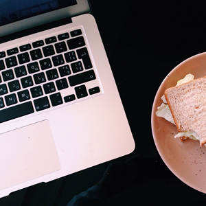 Laptop next to a plate with a sandwich