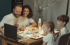 Family of four at a table with a Thanksgiving dinner and a laptop open on the table