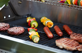 hamburgers, hot dogs, and vegetable kabobs on a BBQ grill