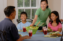 A family of four sitting around a dinner table
