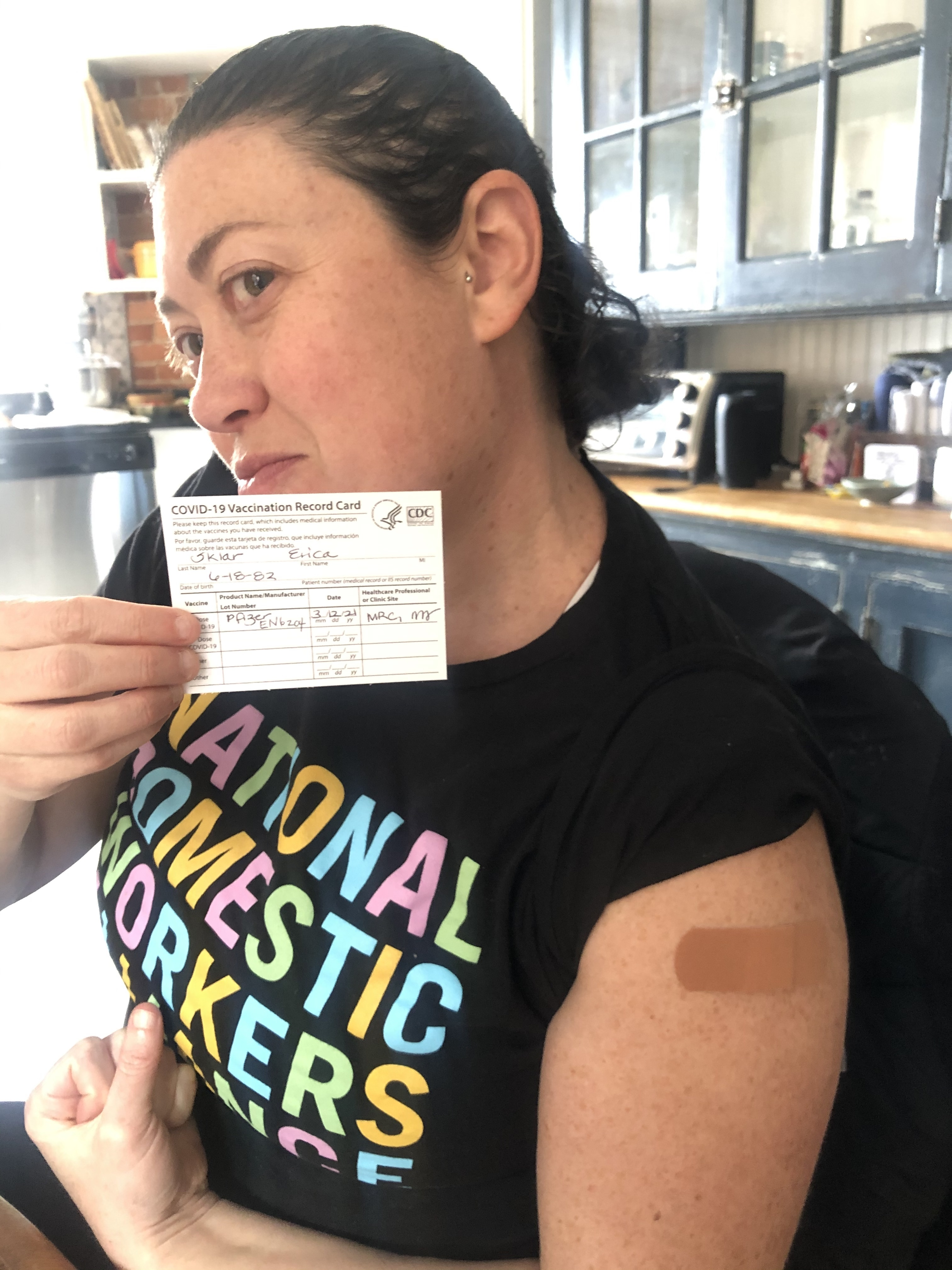 Erica makes a muscle and holds her vaccine card