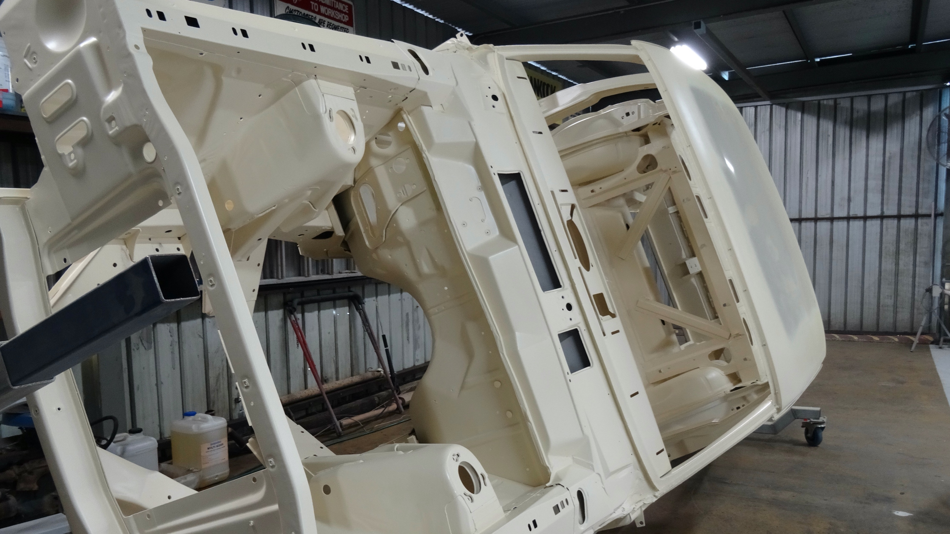 An XT Ford Falcon shell on a vehicle rotisserie awaiting paint and assembly at Blackstar Autocare