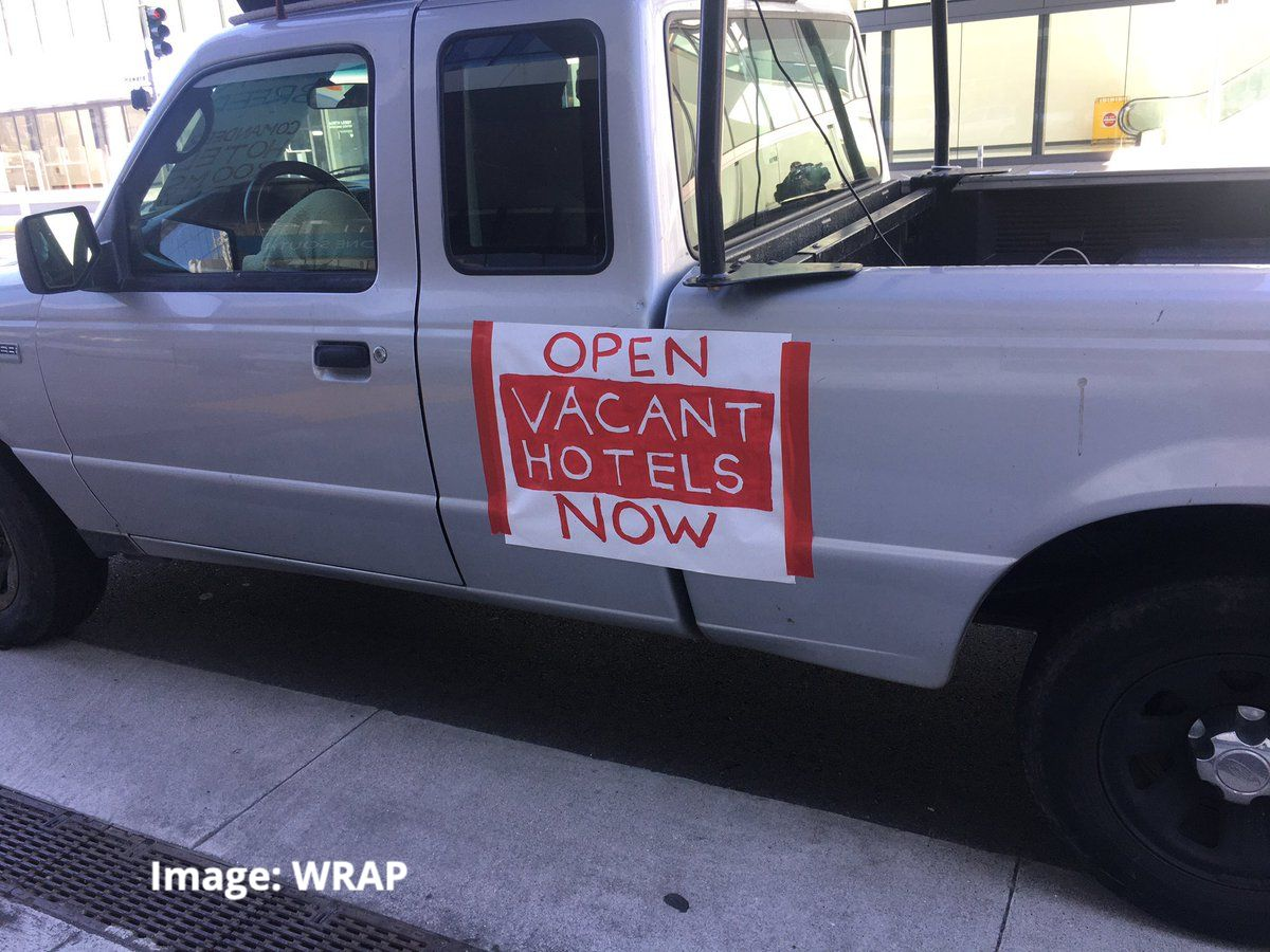 photo of a pickup truck with a painted sign taped to the side that reads: Open Vacant Hotels Now