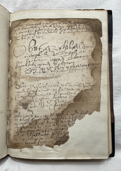 image of a page from a very old book, with handwritten Gaelic text. Much of page is missing but it has been conserved