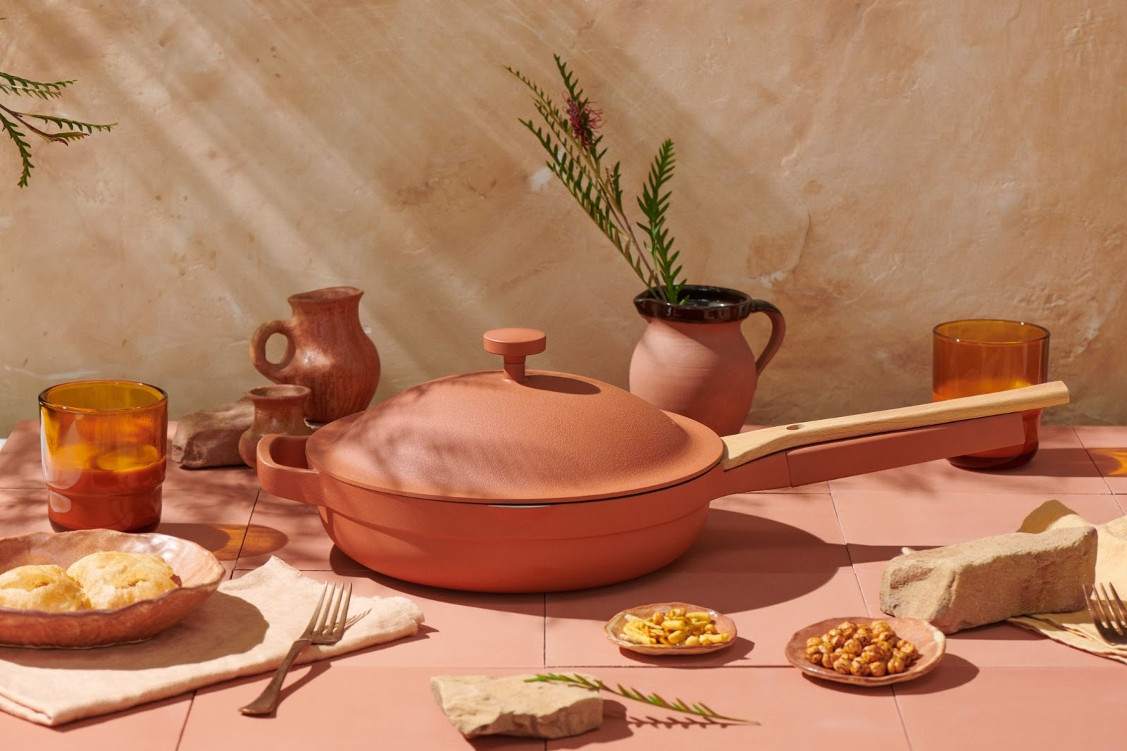 Photo of a terra-cotta colored pan atop a matching table filled with cups and plates of food.