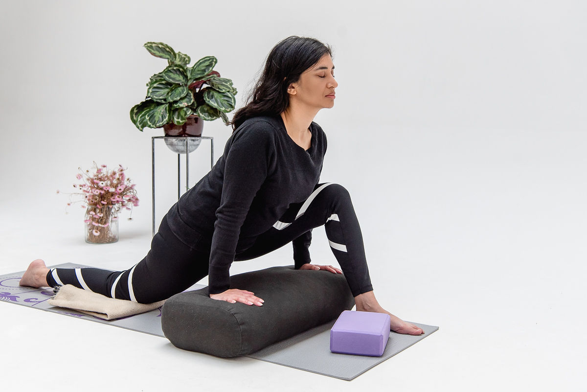 Woman with eyes closed, black hair and dark clothing in a dragon yin yoga pose, hands on a bolster, back knee on a blanket. Purple yoga block by front foot and plants in the background