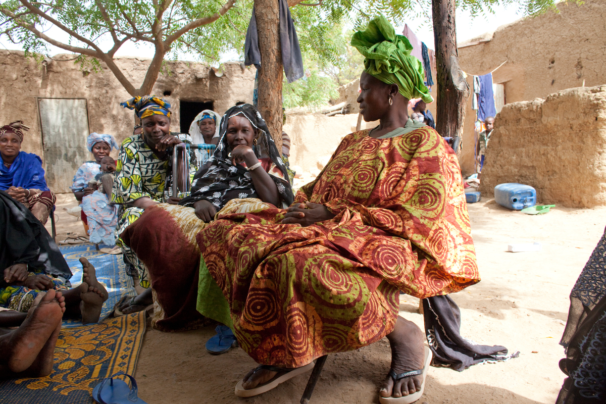 Six beautifuly colorfully dressed black women in a village sitting down discussing something