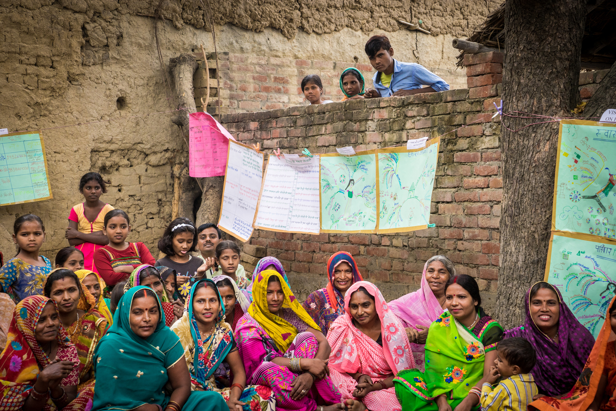 Multi age group of India people in an outside classroom. Seated on the ground dressed in colorful clothing.
