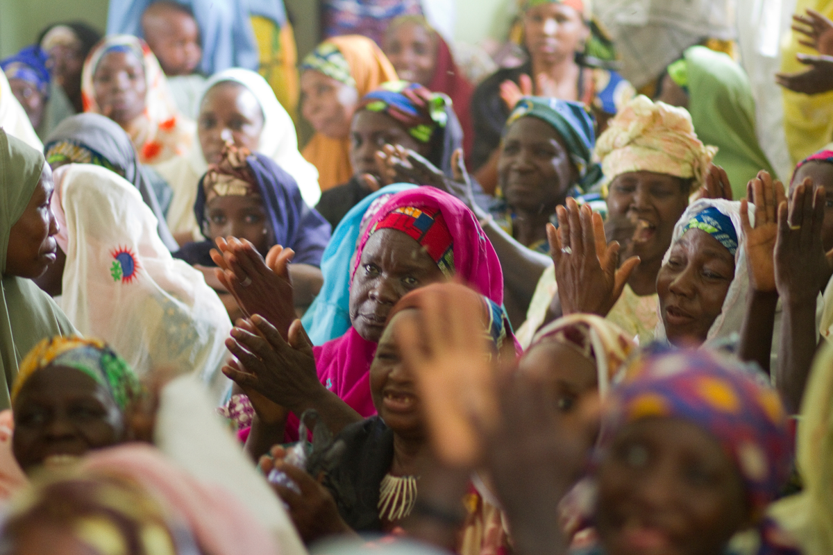Black Women with colorful dresses and head scarfs (gele) clapping.