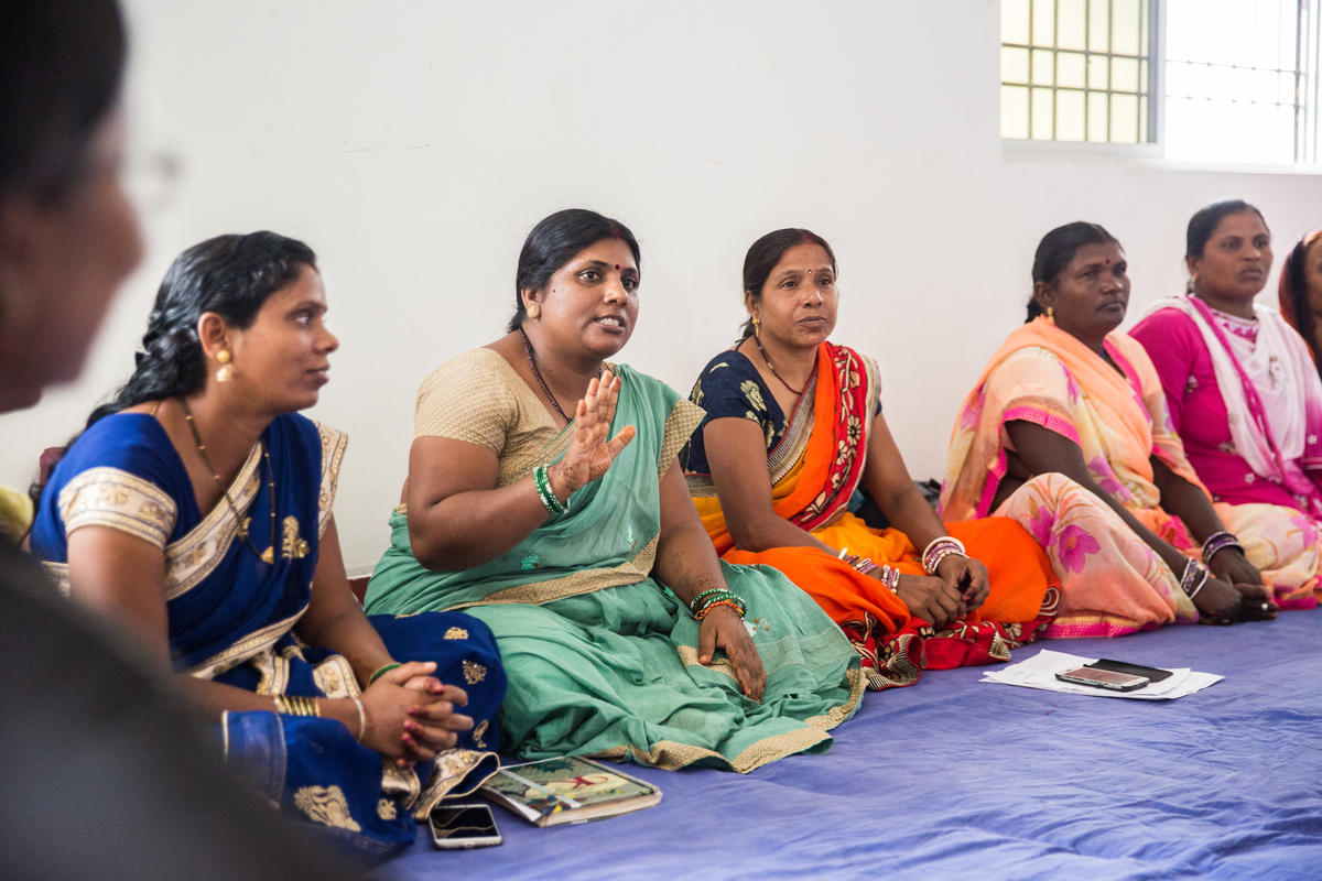 Group of Indian women and sitting on ground inside of a building. One is either raising hand or presenting