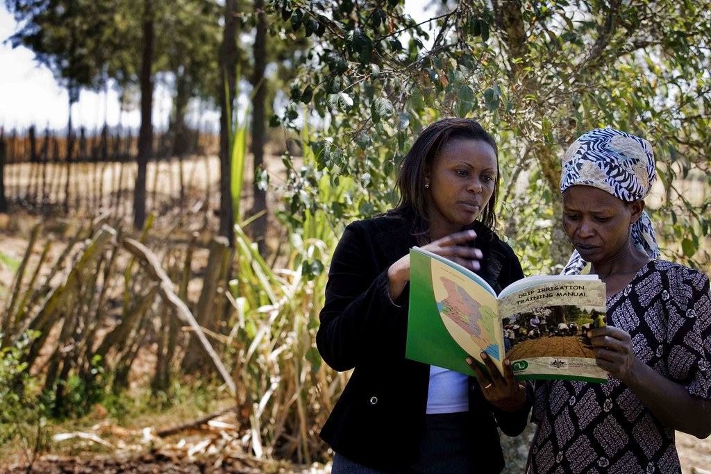 Two woman reading manual or book together standing outside in field.