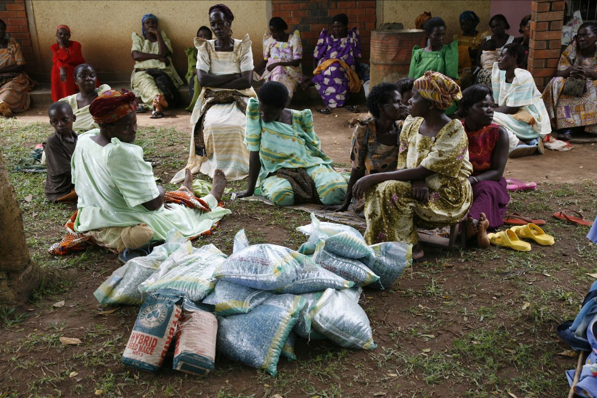Group of African woman and sitting on ground outside of a building. Bags of something next to them.