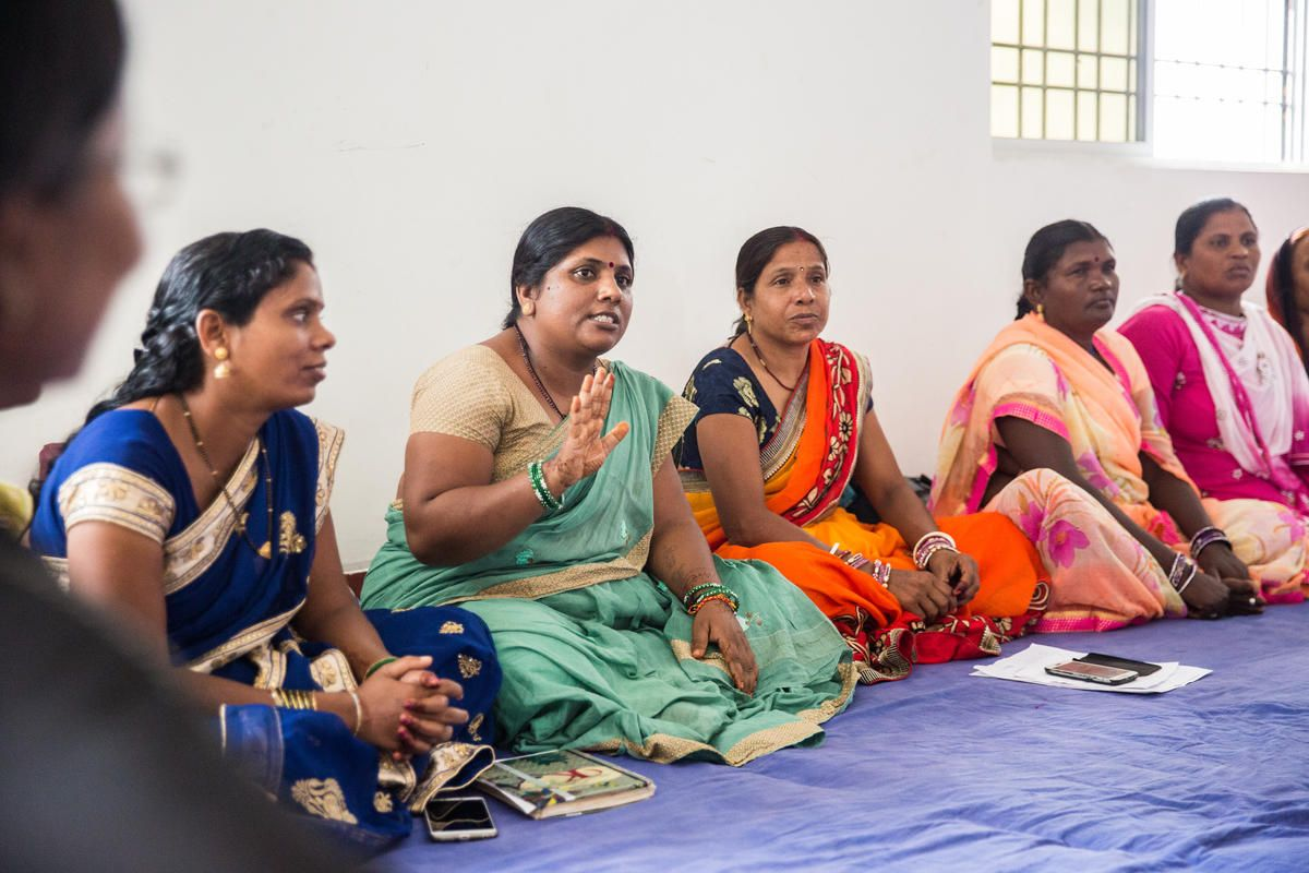 Women sitting in circle, one in speaking with her hand raised
