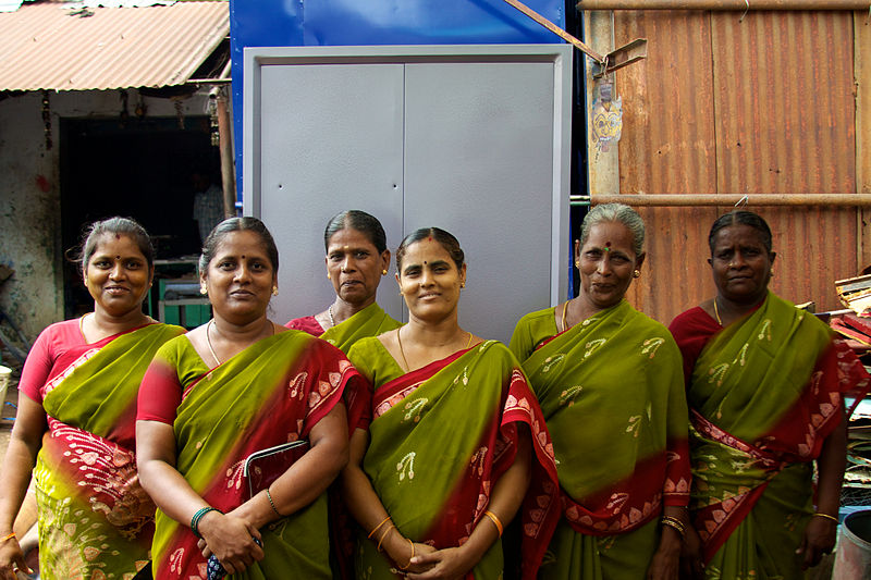 Women dresses in green and red smiling in front of a building