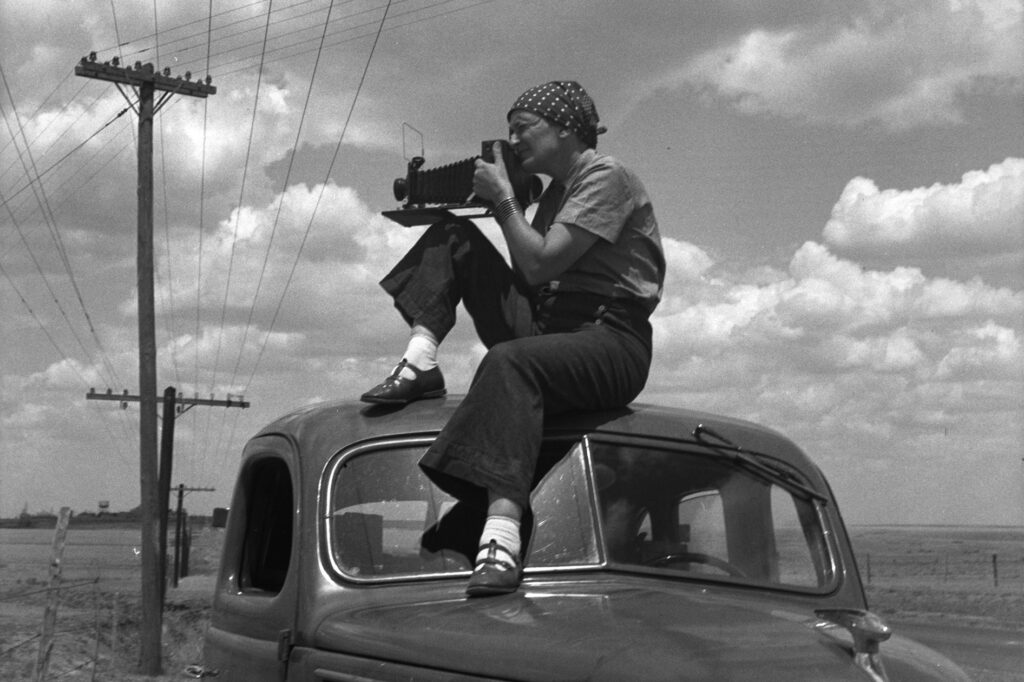 A female photographer sitting on a car