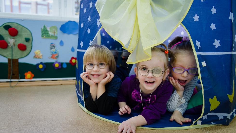 Kindergarten children playing in a tent