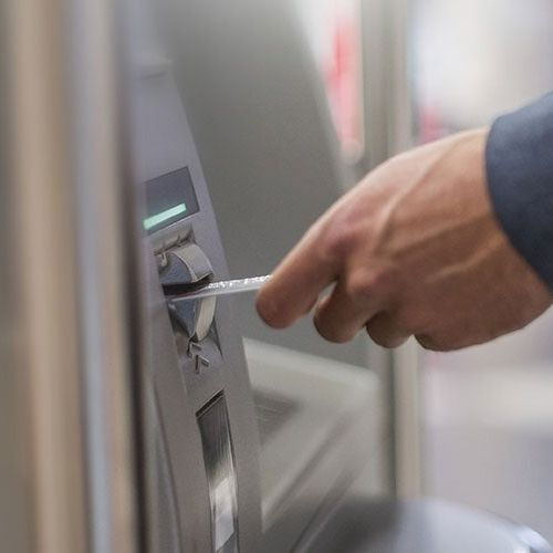 A hand inserting a credit card in an ATM machine